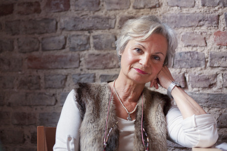 mature people: best ager women looking thoughtful out of window Stock Photo