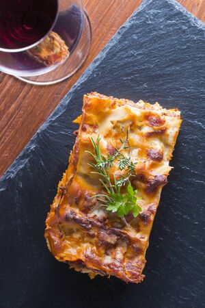 steaming: fresh hot steaming lasagna pasta served on wooden table and slate plate