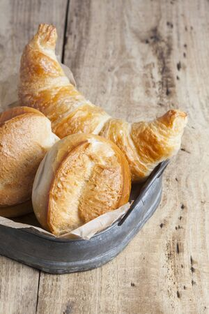 french roll: french breakfast buns bread roll and croissant on vintage tray and wood