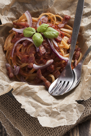 basic food: sphagetti amatriciana italian basic food tomato onion garlic bacon dish on vintage table