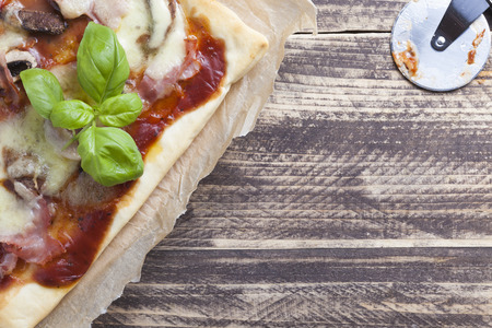 leaf cutter: pizza slice prosciutto funghi ham mushrooms with basil leafs on vintage wood Stock Photo
