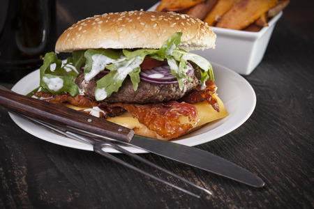 yam: juicy  bacon cheese bbq burger on wooden table with fries