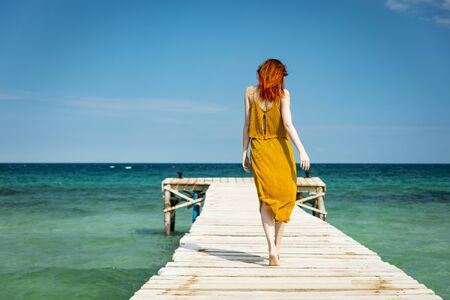 red haired woman at ocean pier in sunny weather