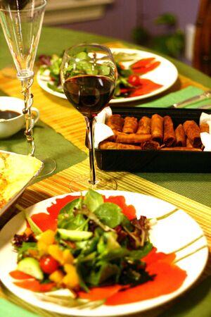 Eggrolls とサラダと赤ワイン 写真素材