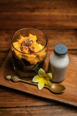 A cup of mango sticky rice on a wooden table