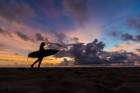 surf girl meets sunset on the beach. silhouette