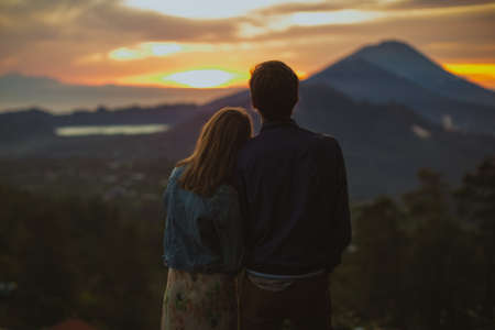 A loving couple, a man and a woman stands near Batur volcano. Sunrise, sunset 版權商用圖片