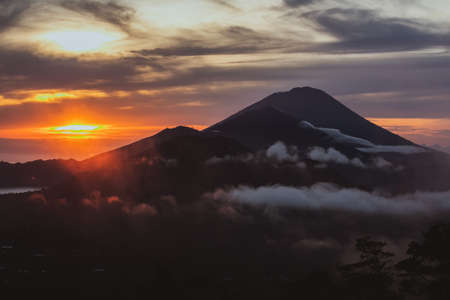 Beautiful landscape with high mountains grey sky and orange sunlight in sunrise