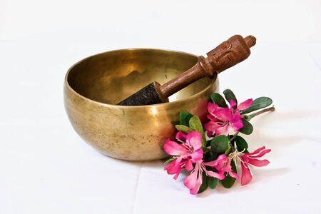 Zingende kom met de bloesem van de bloemkers voor witte achtergrond Stockfoto