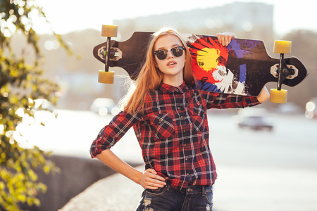 Sport fashion girl posing in summer with skateboard Banco de Imagens