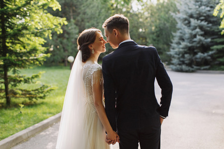 Bride and groom in a park kissing. Happy couple newlyweds bride and groom at a wedding in nature green forest are kissing photo portrait.Wedding Couple