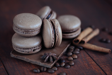 Set of different french cookies macaroons with coffee beans on wooden background. Closeup. Coffee, chocolate tastes macaroons. Copy space Reklamní fotografie