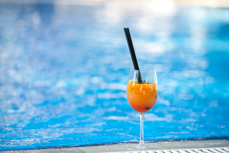 orange cocktail on swimming pool background.Summer vacation concept. Refreshing beverage.horizontal shot. copy space Imagens