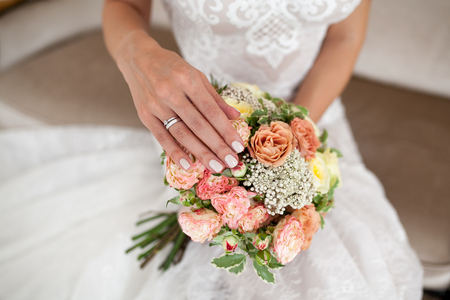 Bride 's hands with beige manicure on wedding bouquet. Close-up.