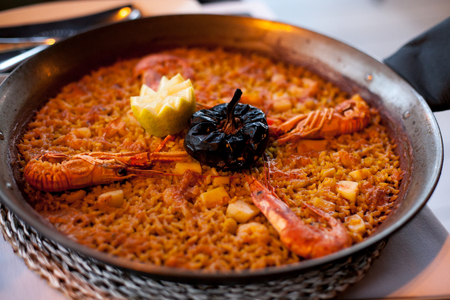 close-up of delicious seafood valencia paella with king prawns, rice with spices and lemon wedges in pan, view from above