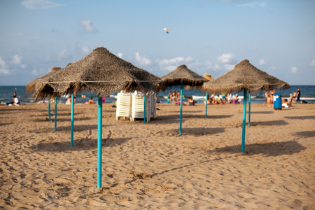 Straw umbrellas on seaside in sunset light. Sand beach in Valencia. Blue sky. Copy space.