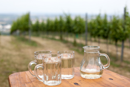 soda spritzer drink refreshment. Three Glass cup of white wine, decanter on wooden table on backgrounds of Vineyards in Heuriger tavern in Eastern Austria, where a local winemaker serves his new wine. Stock fotó