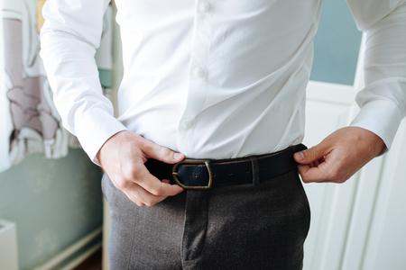 De man met een bruine broek en een wit overhemd maakte een zwarte leren broekriem vast. Formele outfit voor heren. Mode