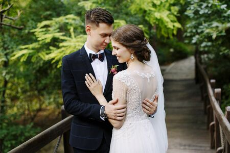 Bride in beautiful wedding dress with open and groom in suit with bow tie posing on the wooden bridge among greenery. Young people embrace and look at each other,happy and smile
