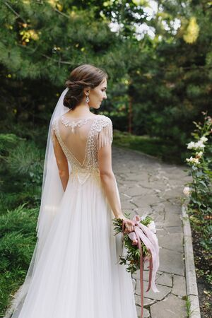 Young brunette bride in a beautiful dress with open back and lace holding a bright wedding bouquet in green park. Rear view, summer, outdoors.fashion 版權商用圖片