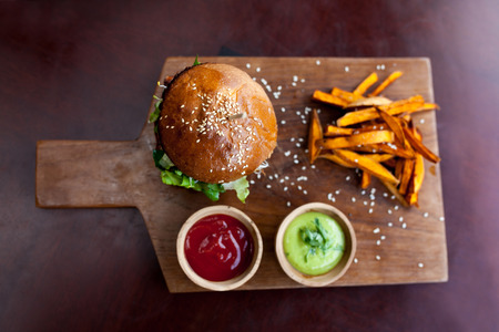 Fast food. Vegetarian burger with sweet potatoes fries and two sauces on wooden cutting board. Tasty sandwich for lunch in cafe. concept of health food. Top veiw.