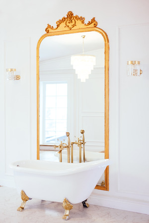 Vintage white color bathroom near mirror with a golden frame. Art decor. Luxury interior