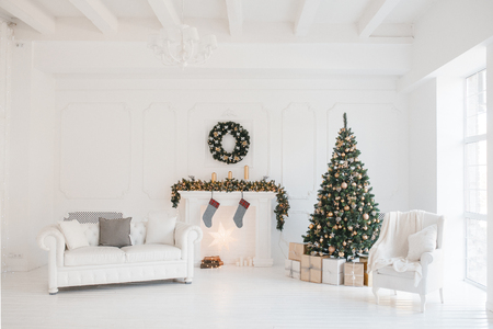 Christmas and New Year decorated white interior room with presents and New year tree and fireplace. Banque d'images