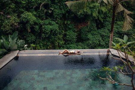 Slim sexy brunette woman in swimsuit relaxing on edge tropical infinity pool in jungle. Palms around, crystal clean water. Luxury resort on Bali island.