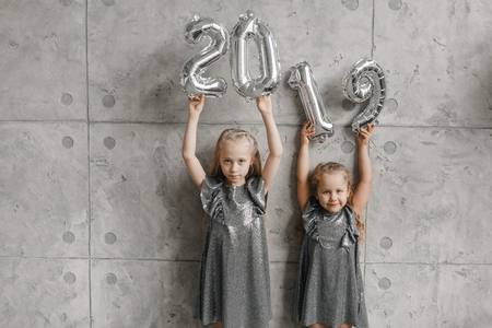 Holding Hands New Years Balloons,. Number 2019. Two smile little girls against grey wall background. Christmas time. New year concept Stock Photo