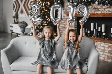 Two smile little girls Holding Hands New Years Balloons,. Number 2019. Christmas time. New year concept Stock Photo