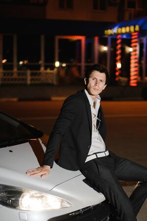 Portrait of a handsome man sitting on car hood of his white cabriolet. Nightlife. Businessman in suit in luxury car.