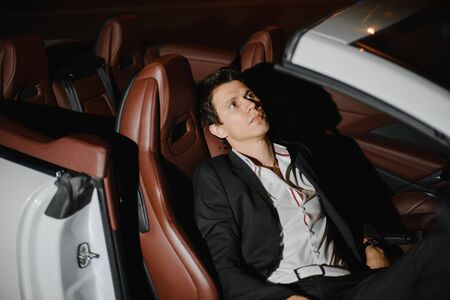 Outdoor portrait of Stylish young man sitting posing in his white cabriolet. Nightlife. Businessman in suit in luxury car. 版權商用圖片