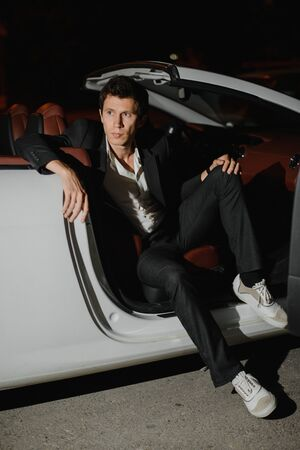 Portrait of a handsome man in white cabriolet. Nightlife. Businessman in suit in luxury car.