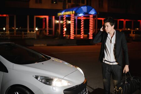 Portrait of a handsome man standing next to his white cabriolet. Nightlife. Businessman in suit in luxury car.
