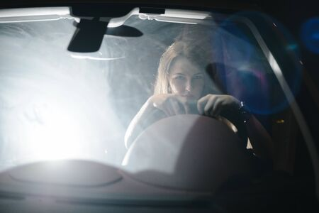 Front view. Portrait of beautiful girl driving her luxury car at night. The traffic lights behind