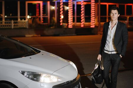 Stylish young man standing next to his white cabriolet. Nightlife. Businessman in suit in luxury car.
