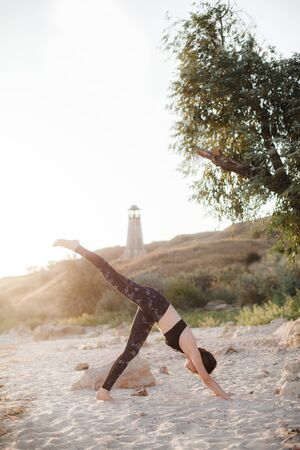 Young Woman Practicing yoga in the nature at sunset on sand beach against of lighthouse. Downward Facing Dog Pose Adho Mukha Svanasana. 版權商用圖片