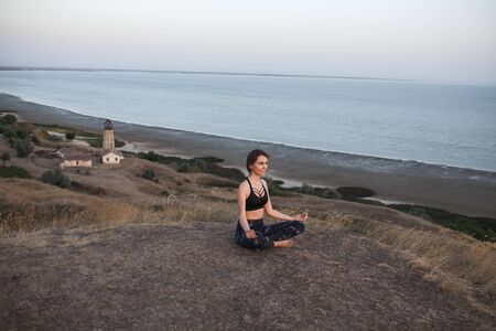 young woman Practicing Yoga in Lotus pose sitting on the edge of rock against of see and lighthouse. Padmasana.