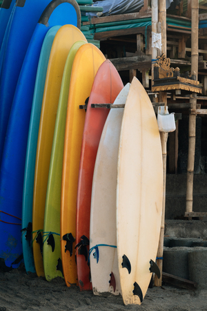 Set of multicolored surf boards in a stack by ocean.Bali.Indonesia. Surf boards on sandy beach for rent. Surf lessons on Weligama beach, Sri Lanka. Imagens - 124949618