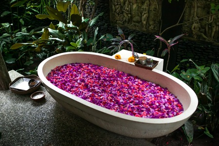 Outdoor bath with tropical pink flowers for relax.Spa,organic an