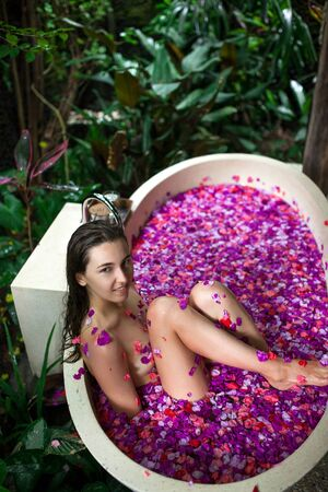 Beauty young Woman relaxing in outdoor bath with tropical flowers.Spa,organic and skin care concept.