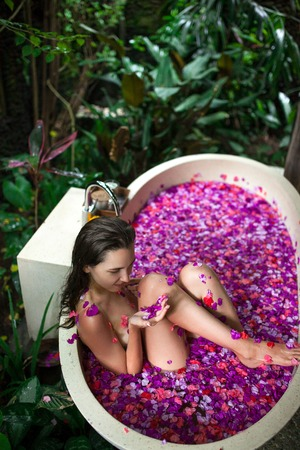 Beauty young Woman relaxing in outdoor bath with tropical flower