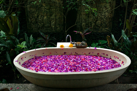 Outdoor bath with tropical pink flowers for relax.Spa,organic and skin care concept.