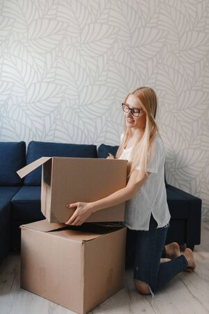 Moving house: Happy woman unpacking box in new home, blonde girl sittng near sofa with boxes.