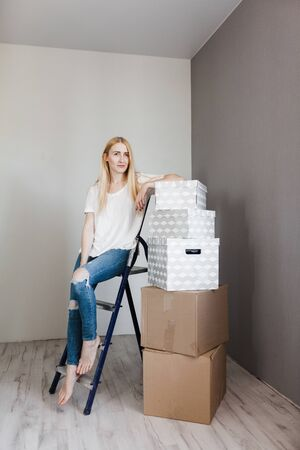 mortgage, people and real estate concept - happy woman with boxes moving to new home.