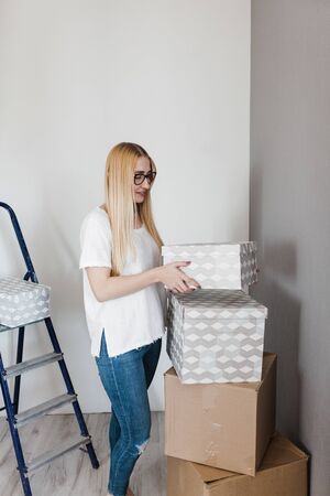 young blonde happy woman in whitet-shirt standing on empty wall with some moving boxes. 版權商用圖片