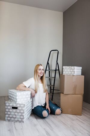 Young woman moving into new apartment holding cardboard boxes with belongings.Photo of young blonde with cardboard box