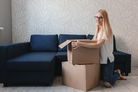 Young woman moving into new apartment holding cardboard boxes with belongings.Photo of young blonde with cardboard box.