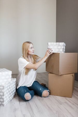 young blonde smile woman surrounded cardboard boxes sitting on floor after relocation. 版權商用圖片 - 138990013