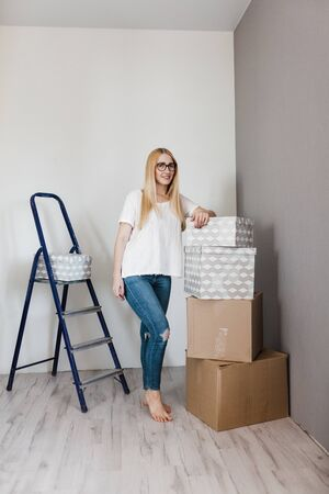 Young woman moving in her new house and doing a home makeover, she is standing near many cardboard boxes around.
